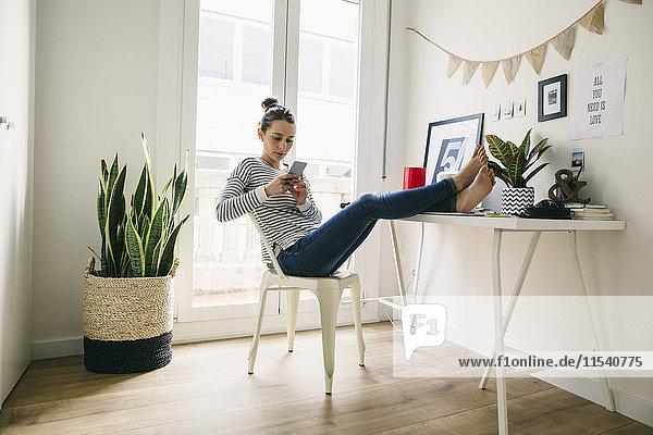 Frau zu Hause  die Füße auf den Tisch legt und auf das Handy schaut