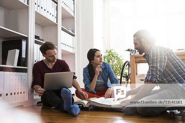Drei kreative Geschäftsleute  die auf dem Boden sitzen und diskutieren