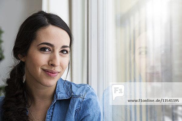 Porträt der lächelnden Frau am Fenster