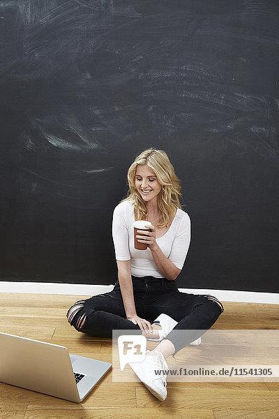 Lächelnder junger Mann sitzt vor der Kreidetafel auf dem Boden mit Laptop und Kaffee zum Mitnehmen.