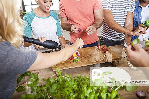 Freunde in der Küche arrangieren Spieße auf Holztablett