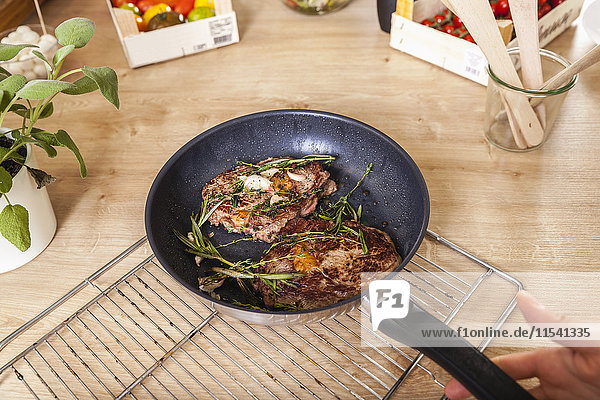 Steak with rosemary in pan