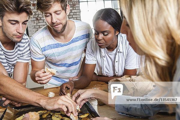Freunde essen Kartoffelspalten aus dem Backblech