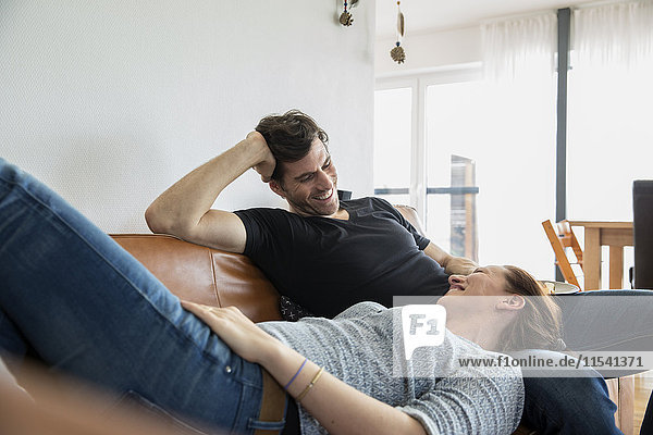 Affectionate couple relaxing at home on sofa
