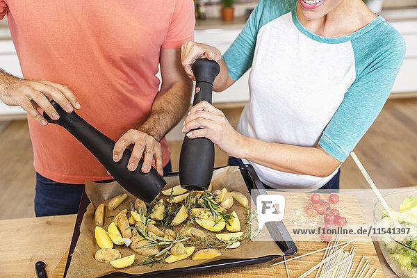 Couple seasoning potato wedges