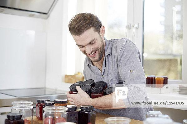 Junger Mann mit Marmeladengläsern in der Küche