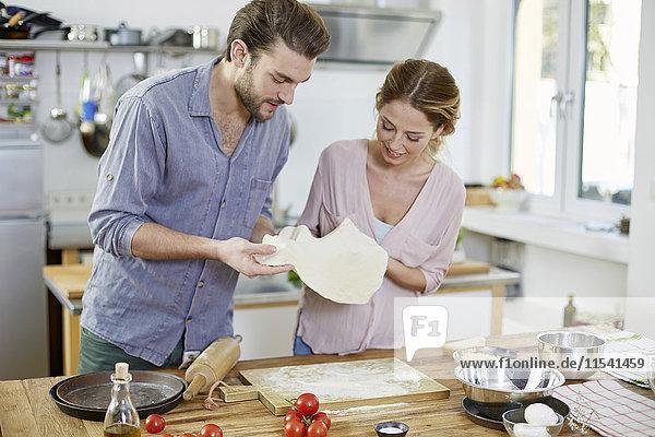 Paar beim Zubereiten von Pizzateig in der Küche