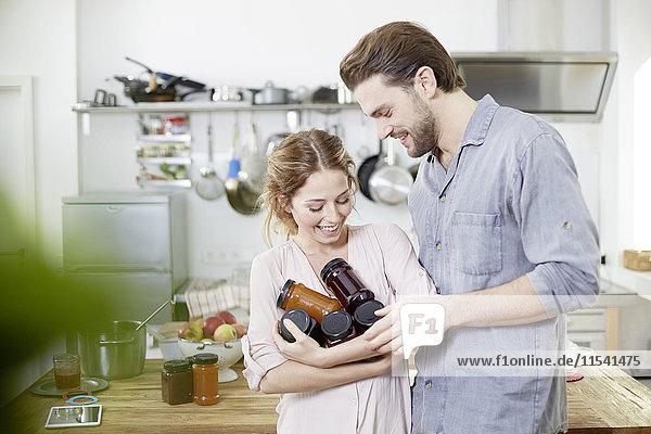 Paar mit Marmeladengläsern in der Küche