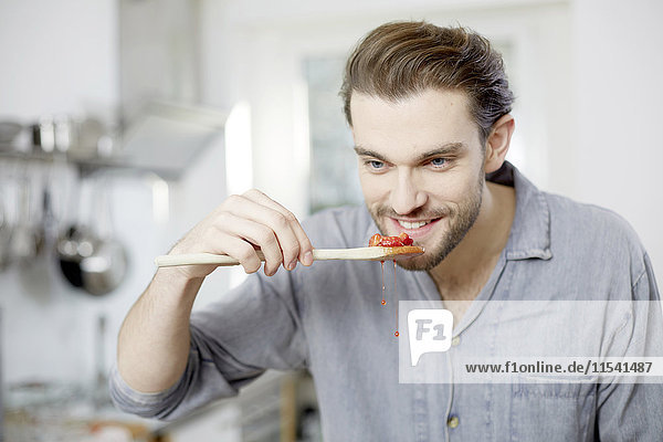 Junger Mann bei der Verkostung gekochter Erdbeeren in der Küche
