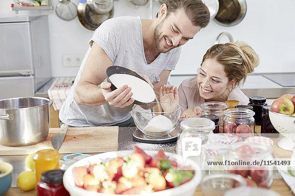 Paar in der Küche Zucker in die Schüssel gießen