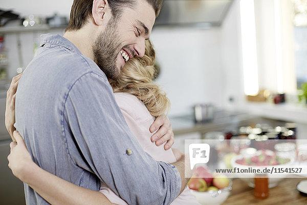 Glückliche Paarumarmung in der Küche