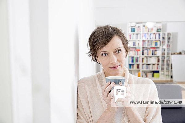 Frau zu Hause hält Tasse