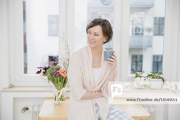Lächelnde Frau zu Hause sitzend auf dem Tisch mit Tasse