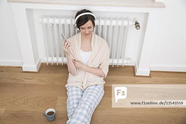 Frau zu Hause auf dem Boden sitzend mit Handy und Kopfhörer