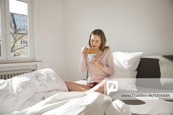 Junge Frau auf dem Bett sitzend mit Kaffee und Croissant