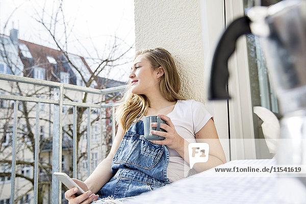 Porträt einer jungen Frau auf dem Balkon mit Smartphone und Tasse Kaffee