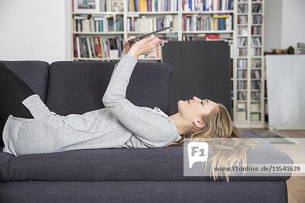 Junge Frau auf der Couch liegend mit digitalem Tablett