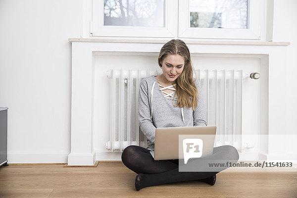 Young woman sitting on the floor in front of heater using laptop