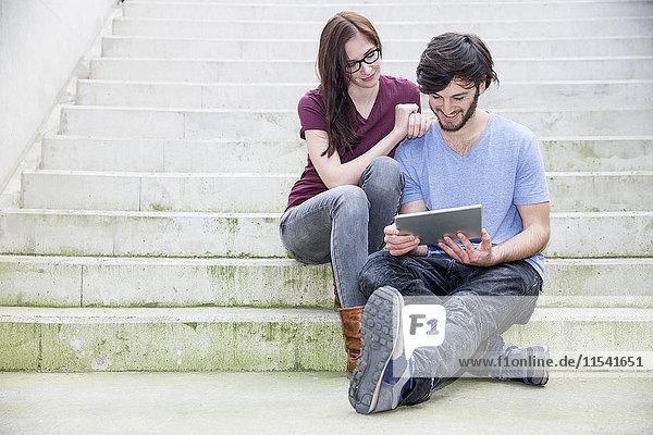 Junges Paar sitzt auf einer Treppe und schaut auf ein digitales Tablett.