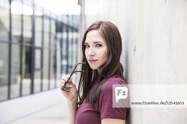Porträt einer jungen Frau  die sich an eine Betonwand lehnt.