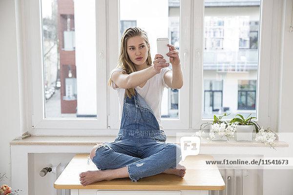 Junge Frau  die zu Hause auf einem Tisch sitzt und Selfie mit dem Smartphone nimmt