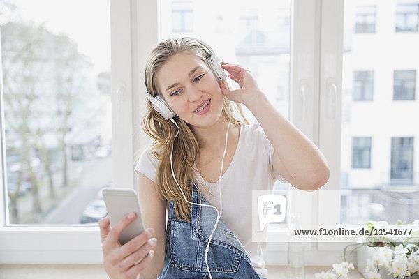 Porträt einer jungen Frau vor dem Fenster Musik hören mit Kopfhörer