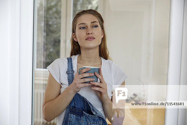 Portrait of young woman with cup of coffee looking through windowpane