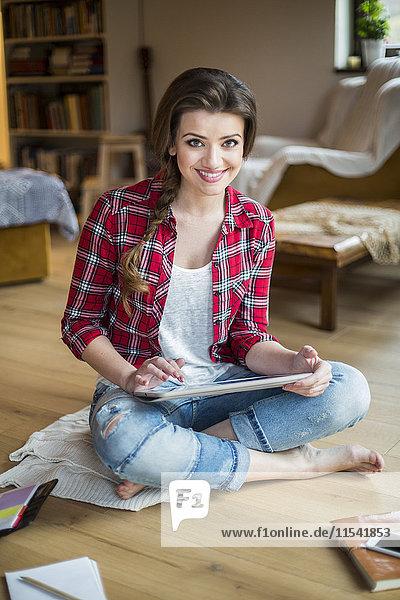 Junge Frau zu Hause bei der Arbeit mit dem digitalen Tablett