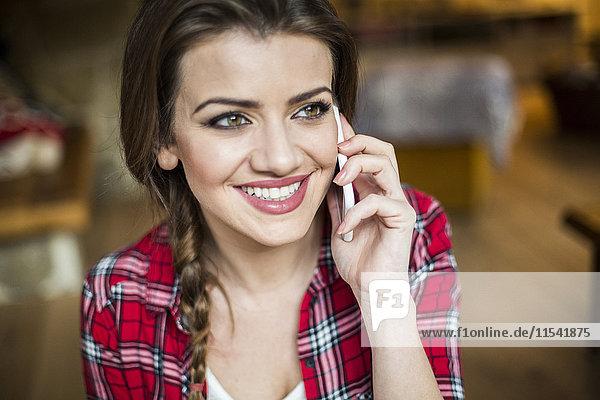 Junge glückliche Frau am Telefon