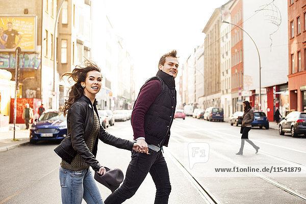 Deutschland  Berlin  glückliches Paar beim Überqueren einer Straße