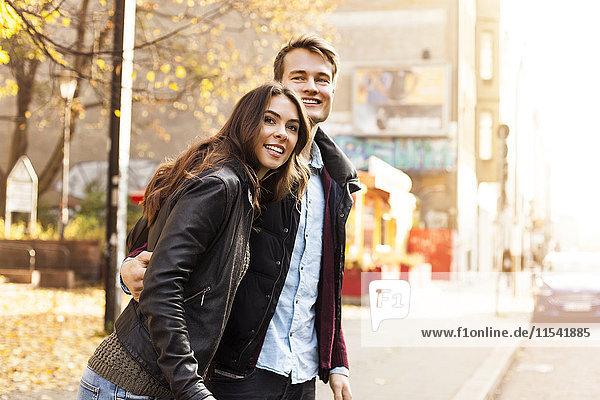 Deutschland  Berlin  glückliches Paar am Straßenrand  das sich umsieht