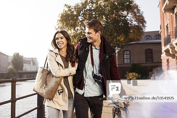 Deutschland  Berlin  glückliches junges Paar  das an der Spree spazieren geht