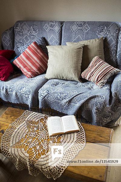 Couch mit Kissen und Deckchen auf Couchtisch