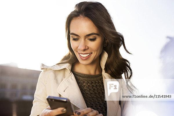 Lächelnde junge Frau mit Smartphone im Freien