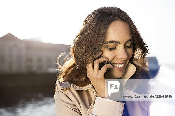 Deutschland  Berlin  junge Frau am Telefon an der Spree