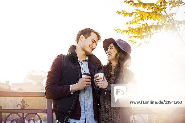 Lächelndes junges Paar mit Kaffee zum Mitnehmen