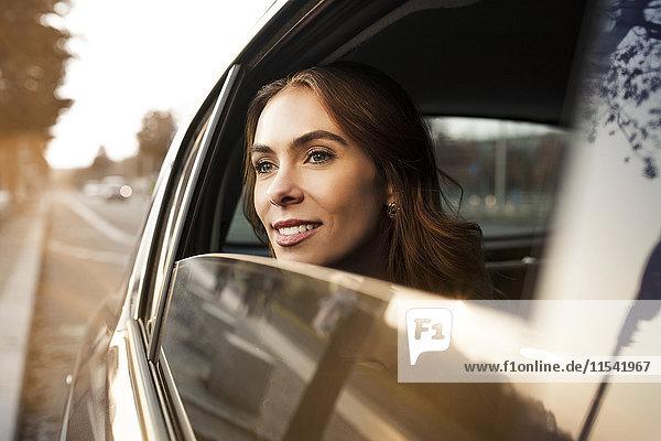 Lächelnde junge Frau schaut aus dem Autofenster