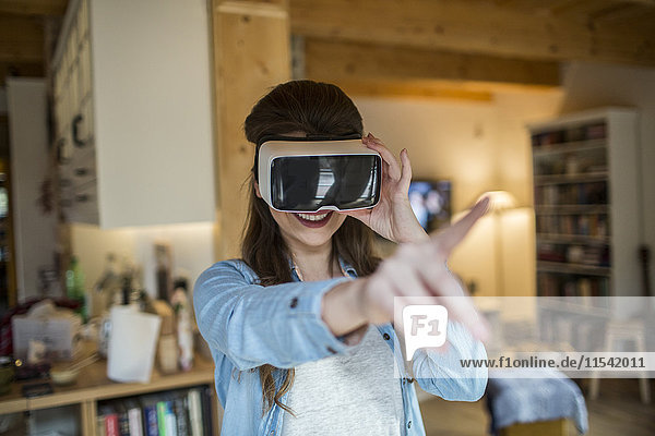 Junge Frau zu Hause mit Virtual Reality-Brille