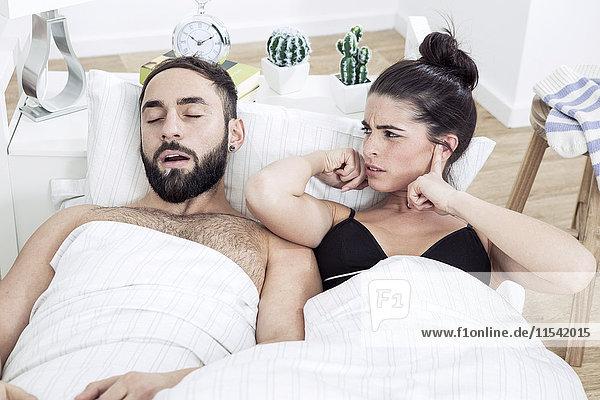 Paar im Bett liegend mit Mann schnarchend