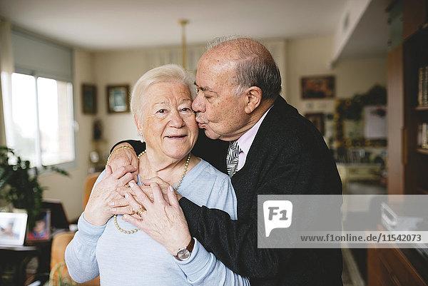 Seniorenpaar  das sich zu Hause umarmt und küsst.