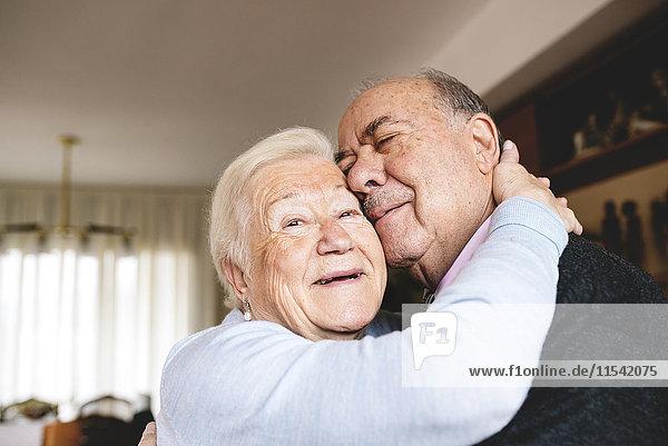 Zärtliche Umarmung eines älteren Paares zu Hause
