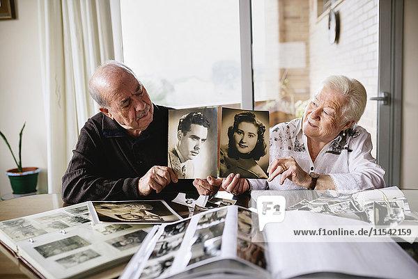 Seniorenpaar zeigt alte Bilder von sich selbst