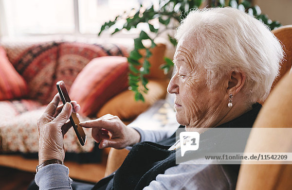 Senior woman sitting in the living room using smartphone
