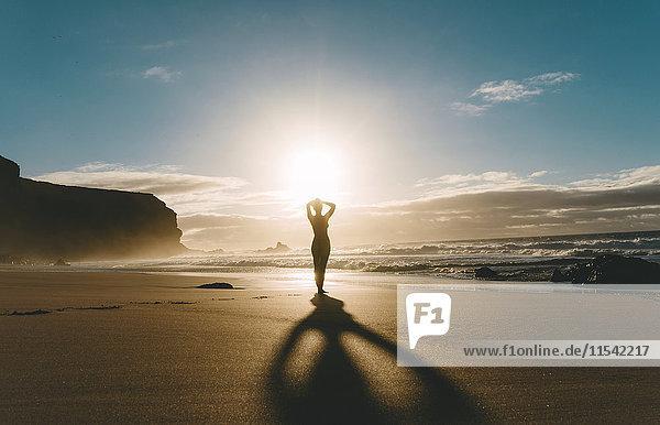 Frau am Strand stehend mit Händen am Kopf bei Sonnenuntergang