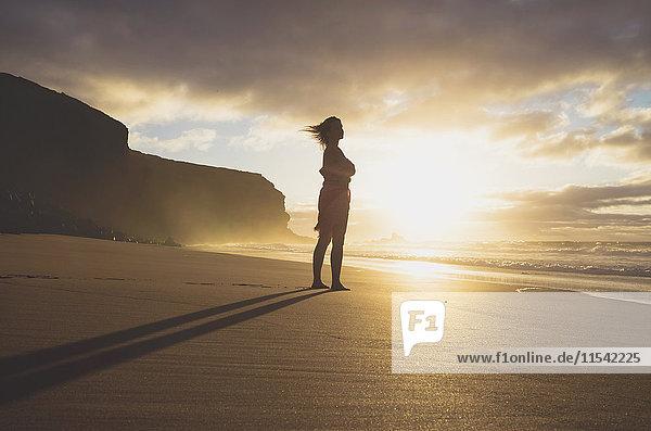 Spanien  Fuerteventura  Frau am Strand stehend bei Sonnenuntergang
