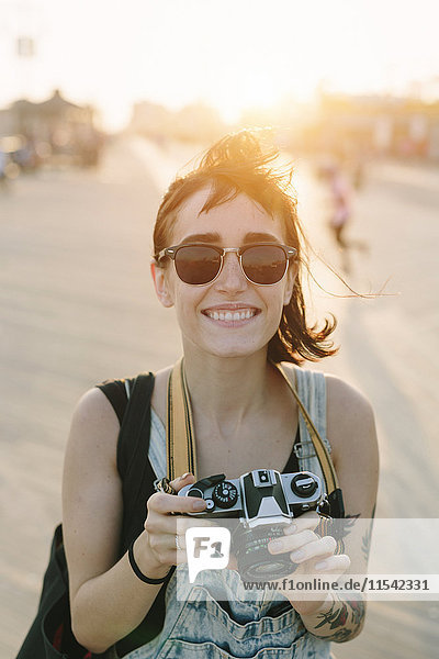 USA  New York  Coney Island  smiling young woman taking photos at sunset