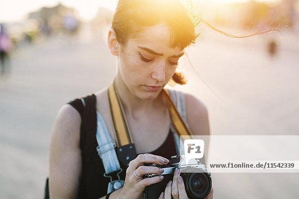 USA  New York  Coney Island  junge Frau schaut bei Sonnenuntergang in die Kamera