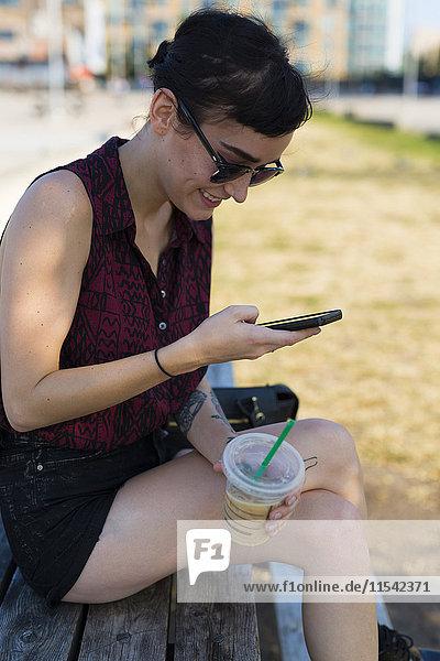Junge Frau sitzt auf einer Bank mit Plastikbecher und schaut auf ihr Smartphone.