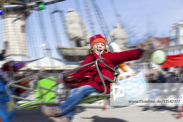 Happy little girl on chairoplane at fun fair