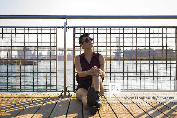 USA  New York City  Williamsburg  portrait of tattooed young woman leaning against railing